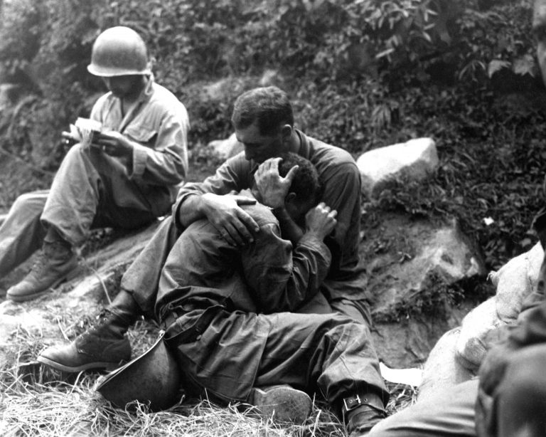 Image of a solider comforting another during the Korean War